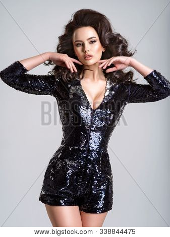Beautiful woman with a sexy slim body.  Beautiful stunning girl  with curly hairstyle. Portrait of  beautiful woman with a long hair.   Fashion model. Gorgeous sensual woman in a black shiny  dress.