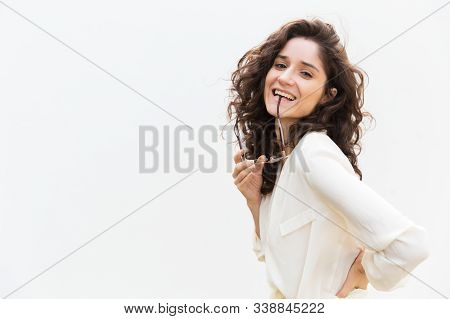 Happy Playful Student Girl Biting Eyewear Temple. Wavy Haired Young Woman In Casual Shirt Standing I