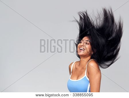 Studio Portrait Of Positive Happy Young Woman Flicking Long Hair
