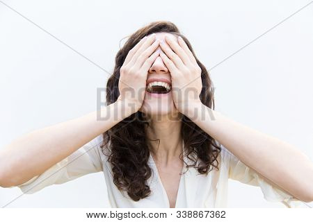 Happy Carefree Woman Covering Face With Hands And Laughing Or Shouting For Joy. Wavy Haired Young Wo