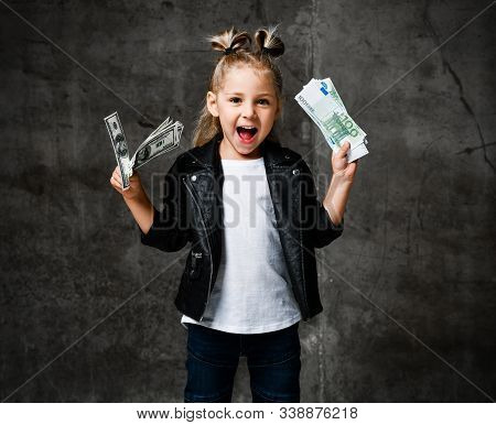 Lucky Rich Kid Girl Millionaire Is Holding In Hands, Shaking, Waving Us Bundles Of Money Euro Hundre