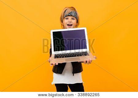 European Boy Holds Laptop Screen Forward With Mockup On Orange Background.