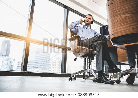 Portrait Of Happy Handsome Business Man With Headset In Modern Office With City Urban Building Backg