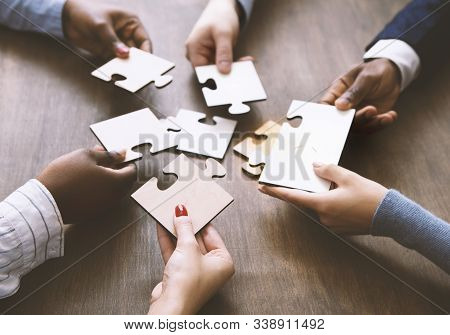Business Solution Concept. Colleagues Assembling Jigsaw Puzzle Together At Office, Close Up