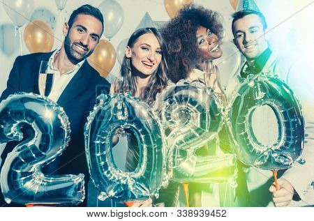 Party people women and men celebrating new years eve 2020 with sparklers and Champagne