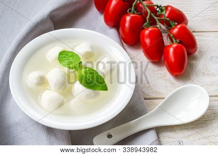 Mini Mozzarella Cheese Balls With Brine, Branch Of Red Cherry Tomatoes And Porcelain Spoon On A  Whi