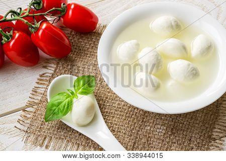 Brine With Mini Mozzarella Cheese Balls In A Bowl, One Mozzarella Ball And Basil In A Spoon And Bran