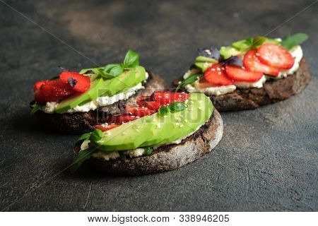 Toast Or Sandwich With Avocado, Cheese, Strawberries, Herbs And Seeds On A Dark Background. An Idea