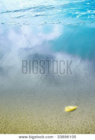 A sandy beach with a yellow pebble
