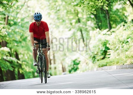 Stamina Test. Cyclist On A Bike Is On The Asphalt Road In The Forest At Sunny Day.