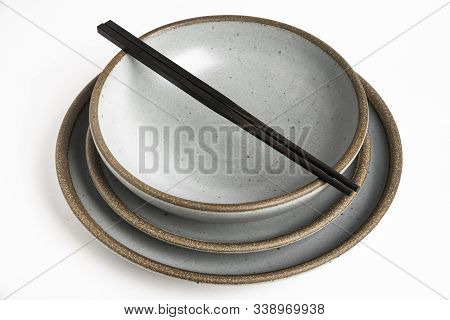 A Pair Of Oriental Black Wooden Chopsticks Resting On A Dinner Service Of Textured Stoneware Plates