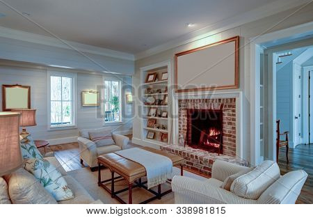 Beautiful living room in expensive home with burning fireplace and large blank picture over the mantle. Place your own art.
