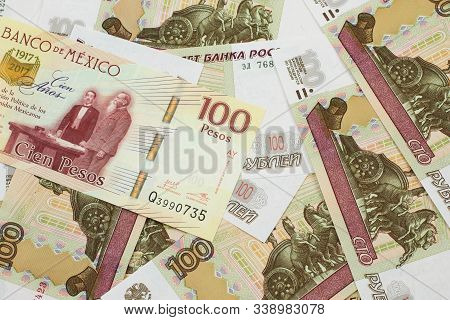 A Close Up Image Of A One Hundred Mexican Peso Bank Note With Russian One Hundred Ruble Bills In Mac