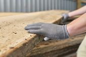Close-up of carpenters hands with plank wood at carpentry woodworking workshop poster