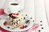 sweet cake with chocolate on plate and cup of coffee on wooden table poster