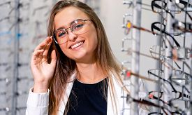 Happy Female Optometrist, Optician Is Standing Near Set Of Glasses. Optical Shop. Stand With Spectac