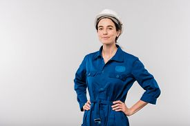 Pretty young successful female engineer in blue workwear and safety helmet keeping her hands on waist in isolation