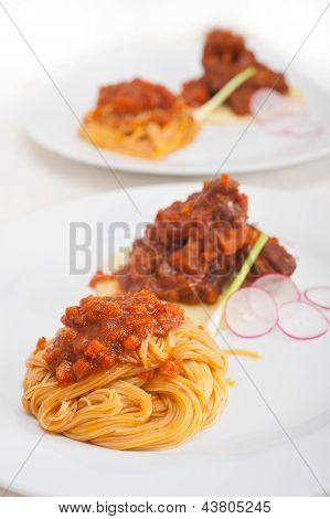 traditional Italian spaghetti pasta with pork ribbs sauce served on polenta bed poster