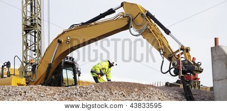 workers, machinery and bulldozer in action inside building site plant
