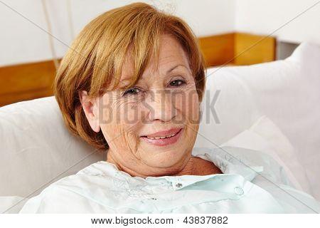 Smiling senior woman sitting in bed in her sleeping room