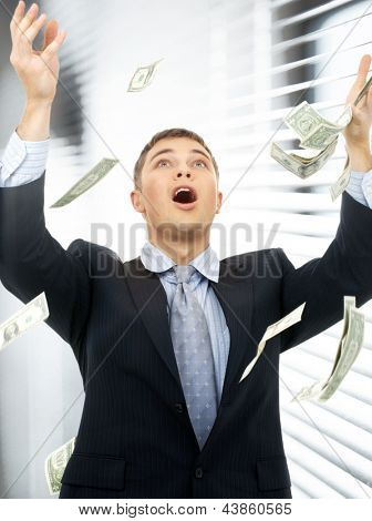 happy successful businessman in money rain indoors