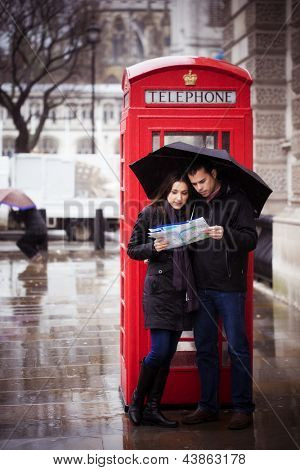 Sweet honeymoon couple consulting map in London