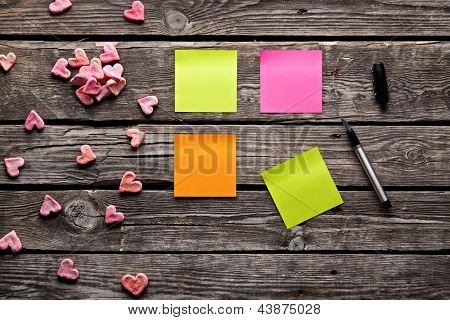 Color sticky note paper sheets with small hearts. Closeup on old wooden table.