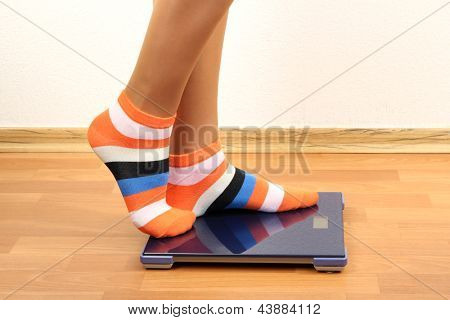 Feet on scales on floor in room
