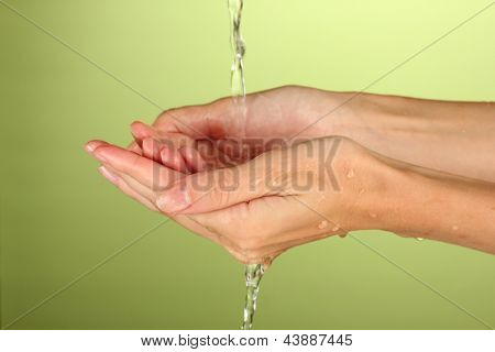 Washing hands on green background close-up