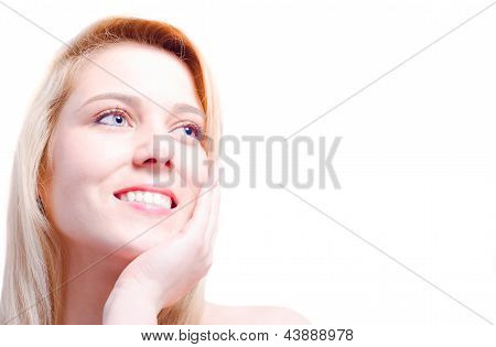 Blonde Beautiful Caucasian Woman Caressing Her Face And Smiling Towards A Copy Space