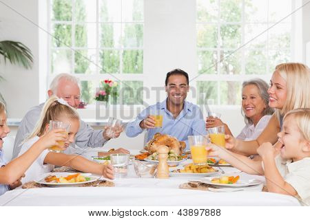Smiling family toasting at thanksgiving at the dinner table