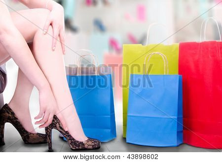 Sexy Woman White Legs With Hand Adjusting High Heels In A Shop Background With Shopping Bags
