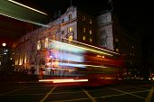 A bright red London bus passing through Piccadilly Circus. poster
