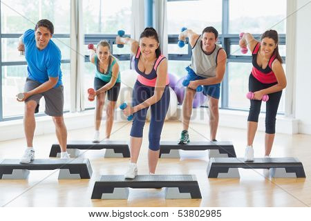 Full length of instructor with fitness class performing step aerobics exercise with dumbbells in a gym