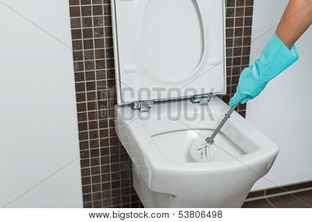 Person Cleaning Under The Rim Of A Toilet Bowl