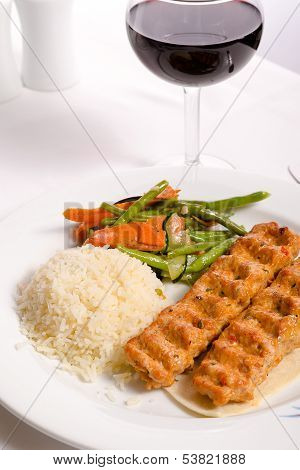 Chicken Adana Kebap Served With Rice Pilaf Vegetables And Red Vine