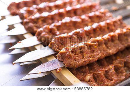 Seasoned Adana Kebabs On Skewers Waiting To Be Cooked