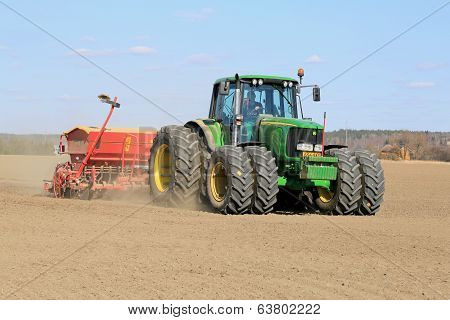 Farmer Working The Field With John Deere Tractor And Seeder
