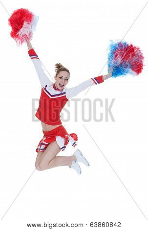 Happy Young Cheerleader Jumping With Pom-poms