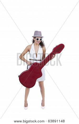 Smiling young female wearing sunglasses posing with guitar