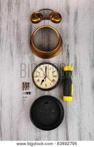 Repair clock on wooden background