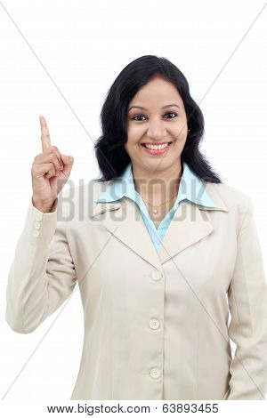 Smiling Business Woman Pointing Up Against White