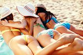 summer holidays and vacation - girls in bikinis sunbathing on the beach poster