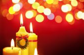 Christmas candle with blurred light on dark background poster