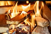 Close up of firewood burning in outdor fireplace poster