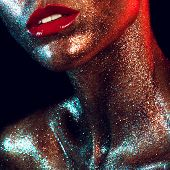 Beautiful girl with gold glitter on her face and red lips poster