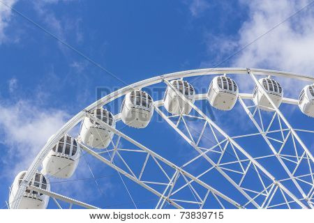 Ferris wheel on a background of blue sky