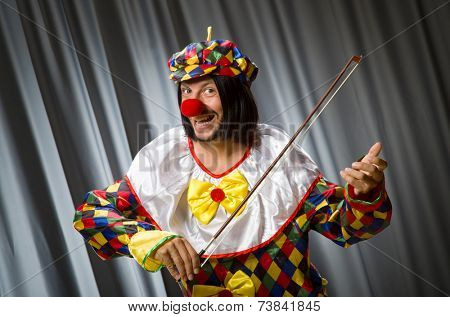 Funny clown playing violin against curtain