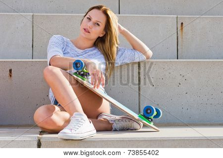 Young, streetwise, woman, sitting on concrete slabs, holding a skateboard on a hot, summer afgternoon