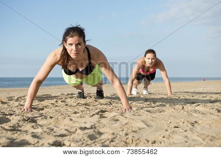 Two women doing pushups on a beach during an intense workout